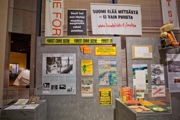 Tempauksia ja kampanjoita metsien suojelutilanteen edistämiseksi. Vasemmalla pilkottaa retkeilyä esittelevä näyttelyosio.